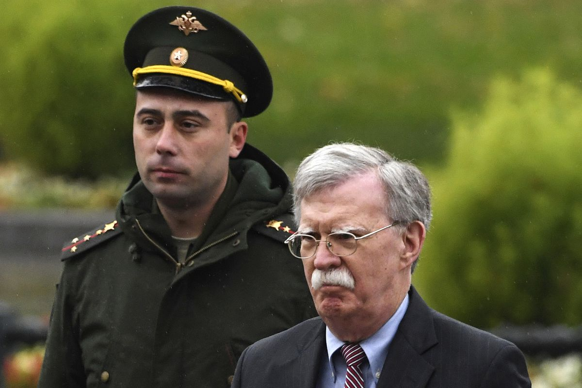 U.S. National Security Adviser John Bolton, right, attends a wreath laying ceremony at the Tomb of the Unknown Soldier by the Kremlin wall in Moscow, Russia, Tuesday, Oct. 23, 2018. U.S. President Donald Trump's national security adviser Bolton struck a conciliatory note Tuesday in talks in Moscow, just days after Trump vowed to pull out of a key arms control treaty with Russia. (Kirill Kudryavtsev/Pool Photo via AP)