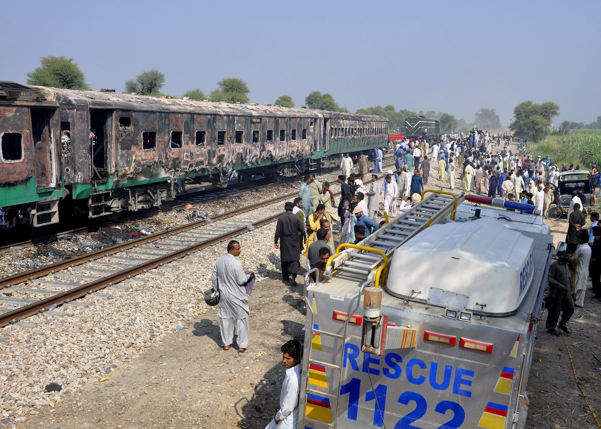 Pakistani soldiers and officials examine a train damaged by a fire in Liaquatpur, Pakistan, on Thursday, Oct. 31, 2019. A massive fire engulfed three carriages of the train traveling in the country's eastern Punjab province. (AP Photo/Siddique Baluch)