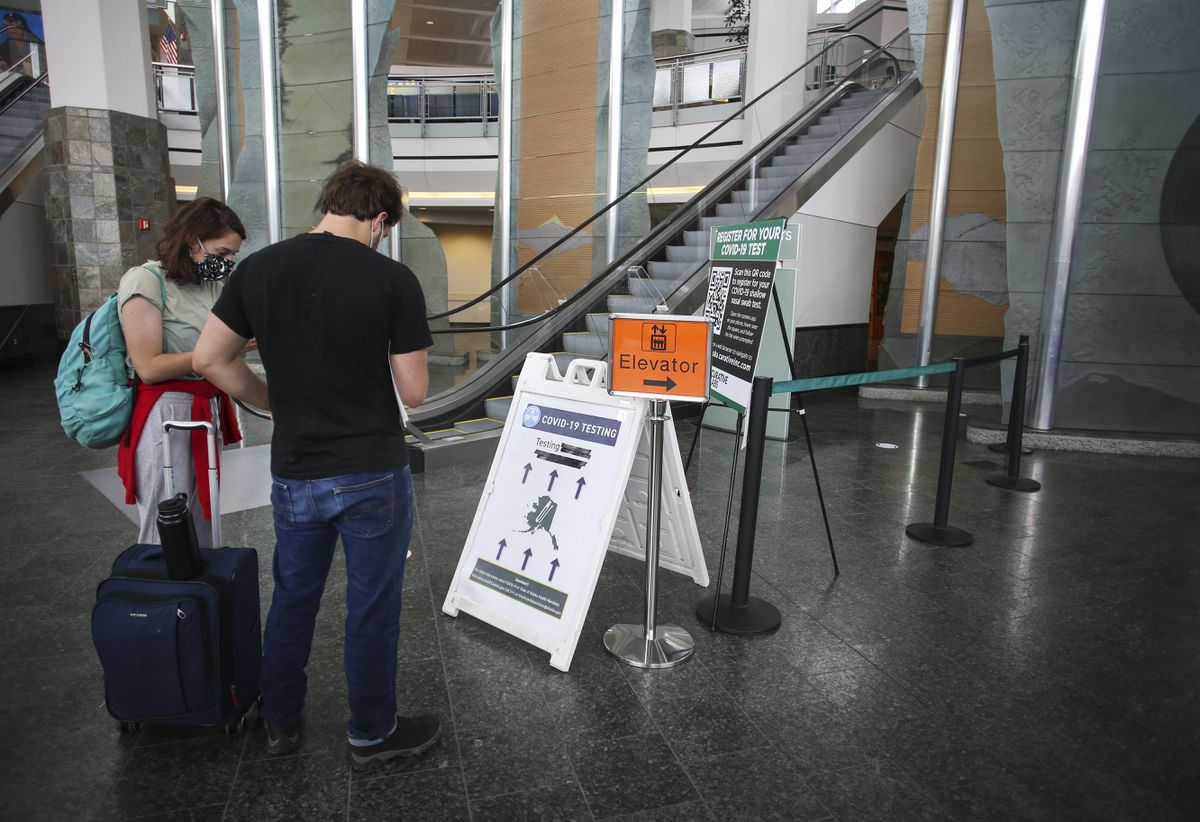 Passengers read COVID-19 testing instructions at the testing site in the Ted Stevens Anchorage International Airport on July 17, 2020. (Emily Mesner / ADN)