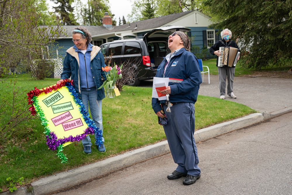 Mr. Whitekeys, former owner of the Fly By Night Club in Spenard and host of the Whale Fat Follies musical revue, plays the accordion as Judith Haggar helps carry flowers and a sign for mail carrier Weeze Smoke on Saturday, May 23, 2020 in Turnagain. Smoke has delivered the mail in this neighborhood for the past 15 years and today is her last day on the job before retiring. (Loren Holmes / ADN)