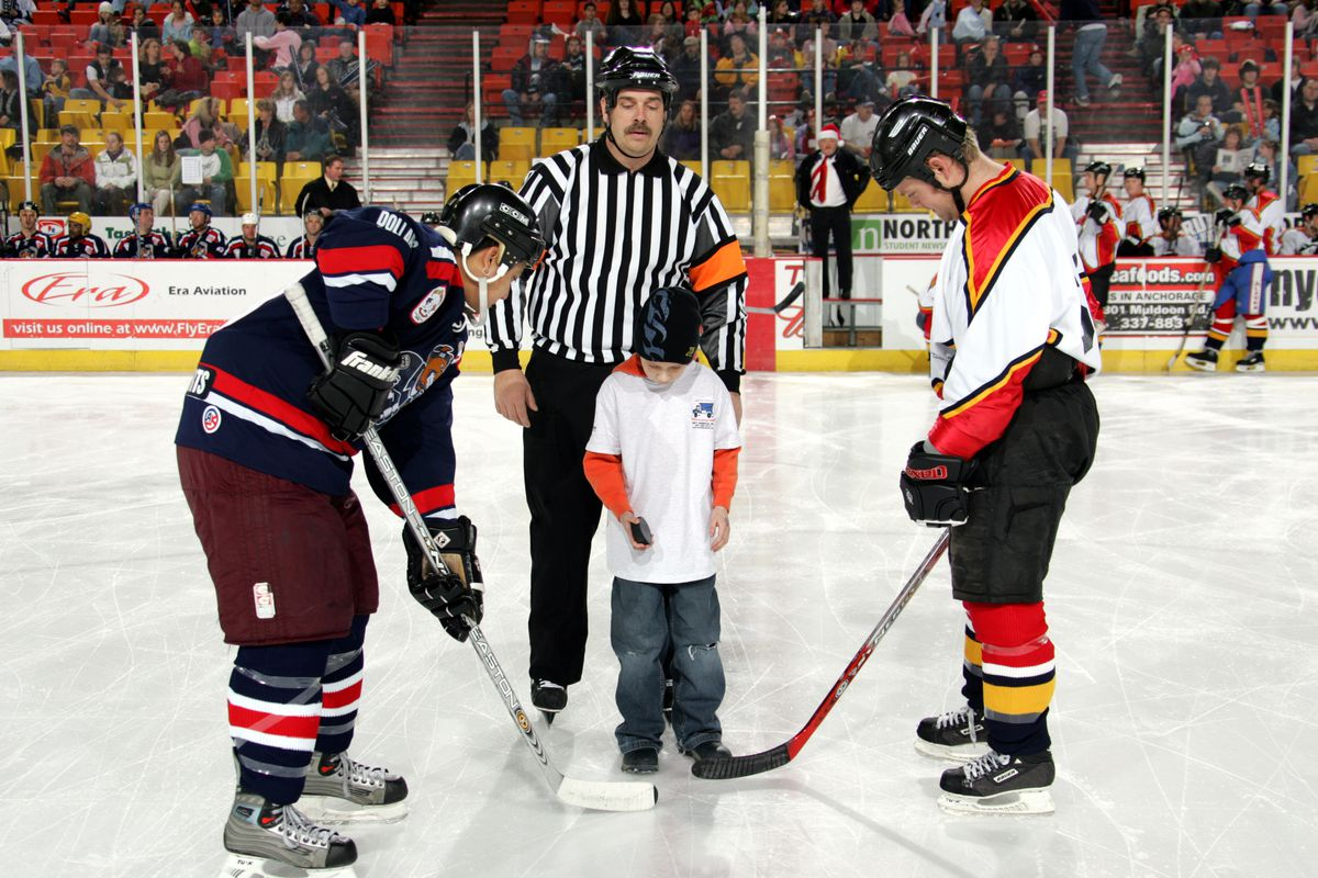 "APD's Jon Lamebull and AFD's Eric Tuott watch as Tison Young drops the puck before the start of the sixth annual ""Guns 'N' Hoses"" hockey game. The charity event will take place this Saturday at the Sullivan Arena. (Photo by Cathy Diehl-Robbins/APD)"