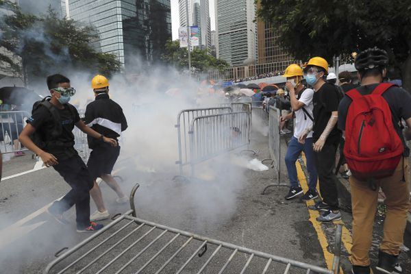 Protesters react to tear gas during a large protest near the Legislative Council in Hong Kong, Wednesday, June 12, 2019. Hong Kong police have used tear gas and high-pressure hoses against thousands of protesters opposing a highly controversial extradition bill outside government headquarters. (AP Photo/Kin Cheung)
