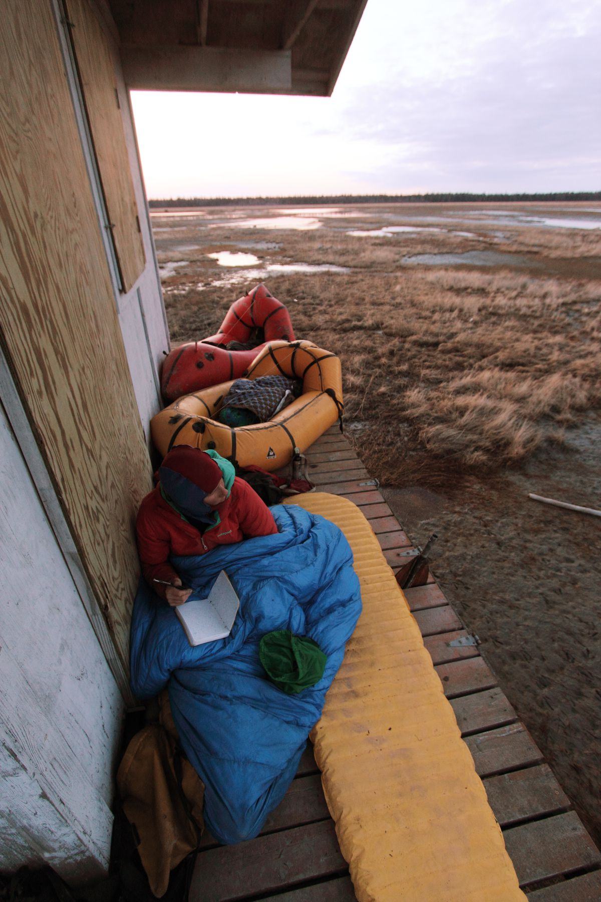 Erin McKittrick writes in her journal from the porch of a duck shack on the Susitna Flats in Southcentral Alaska in May of 2013. The shack was locked, but the trekkersmade use of its porch for an unorthodox campsite. (Photo by Ground Truth Trekking)