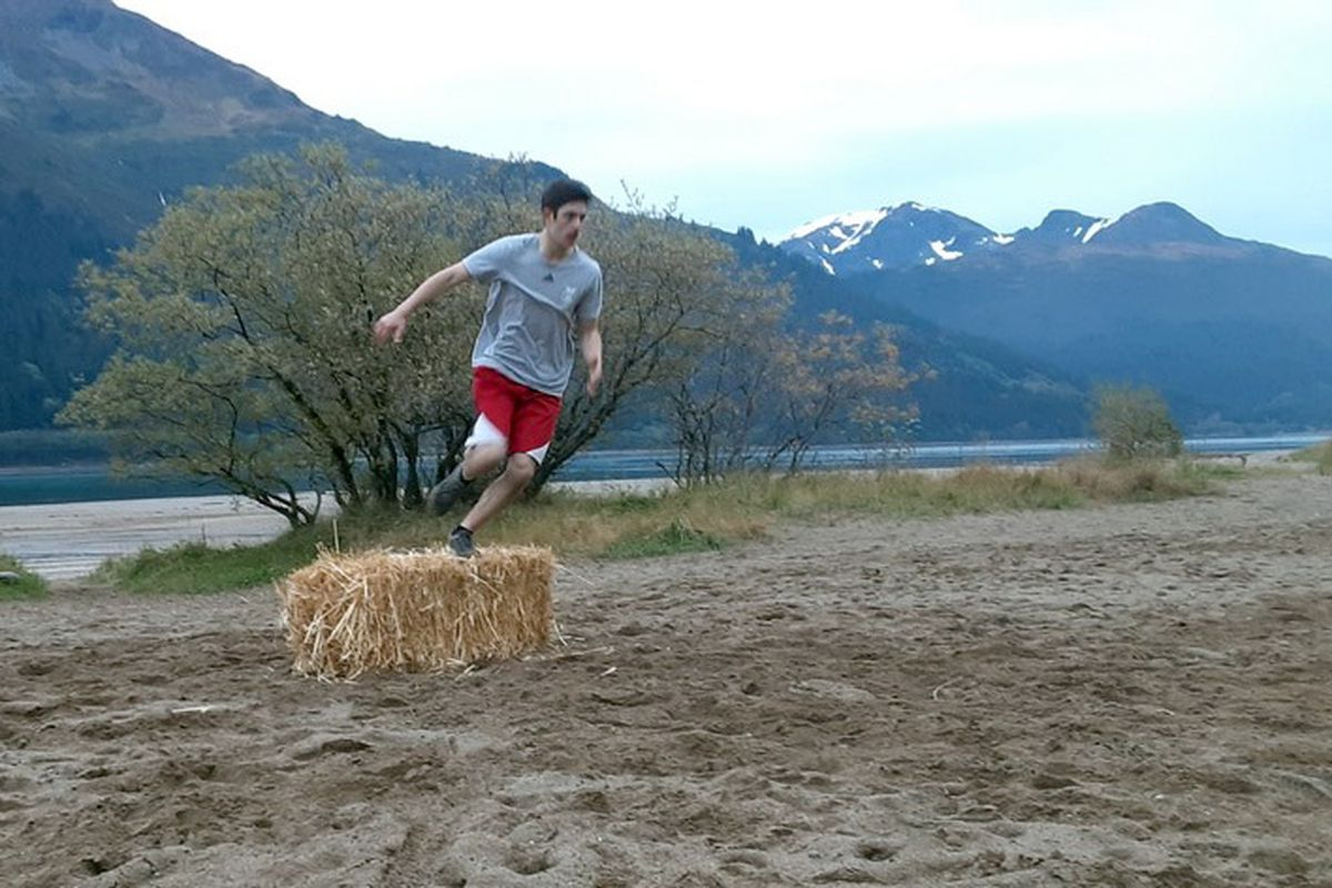 Ben Coutu, a senior on the Juneau-Douglas cross-country team, jumps over a bale of straw during the Sayéik Showdown relay race Tuesday in Juneau. (Photo by Abby Jahn)