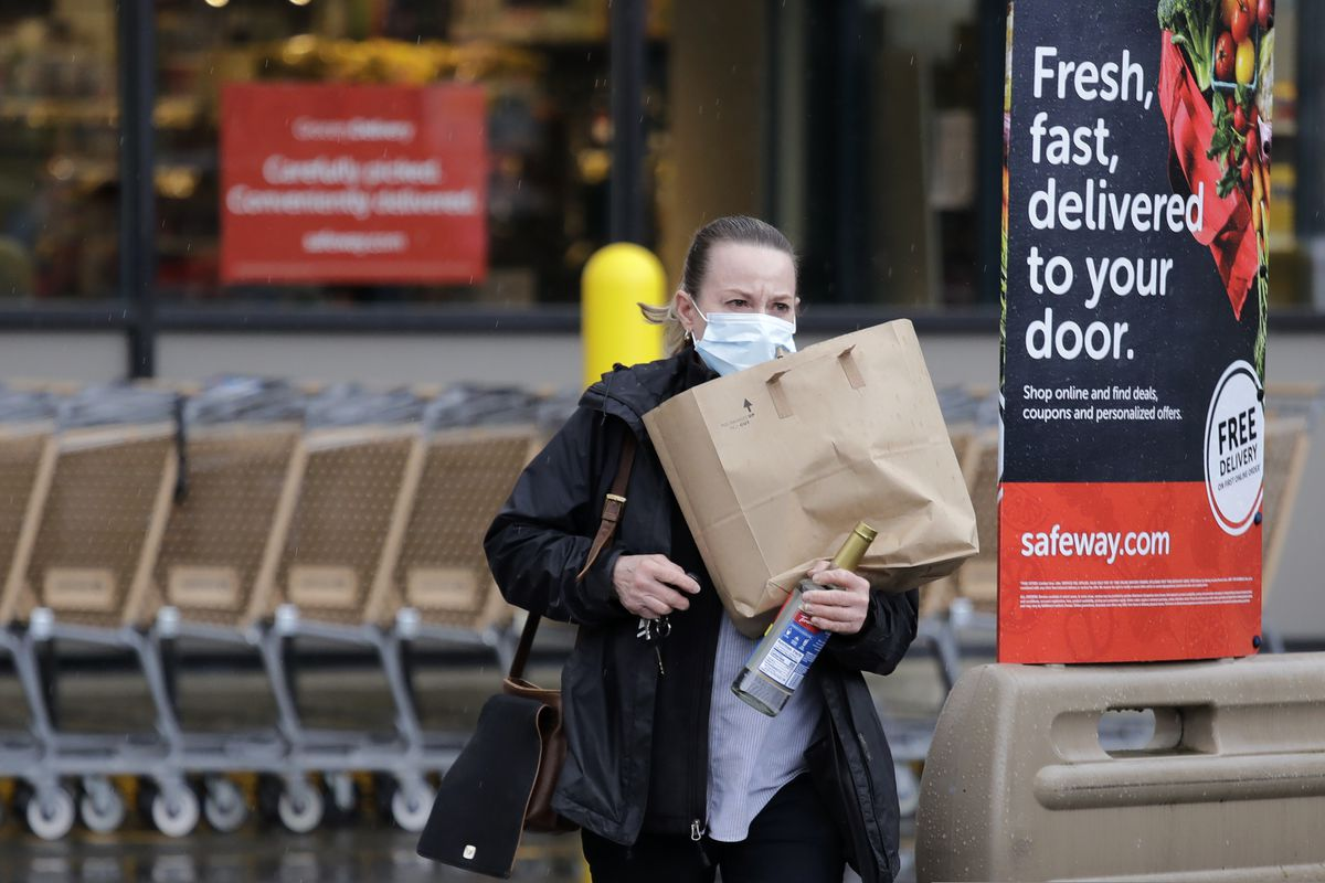 In this Monday, March 30, 2020, photo, a shopper leaves a grocery story with food packed in a paper bag, where the dime-per-bag fee has been waved during the coronavirus outbreak, in Seattle. Just weeks earlier, cities and even states across the U.S. were busy banning straws, limiting takeout containers and mandating that shoppers bring reusable bags or pay a small fee. Grocery clerks are nervous that the virus could linger on reusable fabric bags and their unions are backing them up with demands to end plastic bag fees and suspend bag bans. The plastics industry has seized the moment, lobbying to overturn existing bans on single-use plastics. (AP Photo/Elaine Thompson)