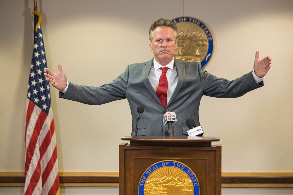 Gov. Mike Dunleavy speaks at a press conference on Tuesday, Aug. 13, 2019 where he announced a 3-year, $70 million budget cut to the University of Alaska. He is stretching his arms wide to illustrate the initial scope of his administration's disagreement with the university after he had originally vetoed $130 million in state funding for UA for the current fiscal year that started July 1, atop a $5 million cut approved by the Legislature. (Loren Holmes / ADN)