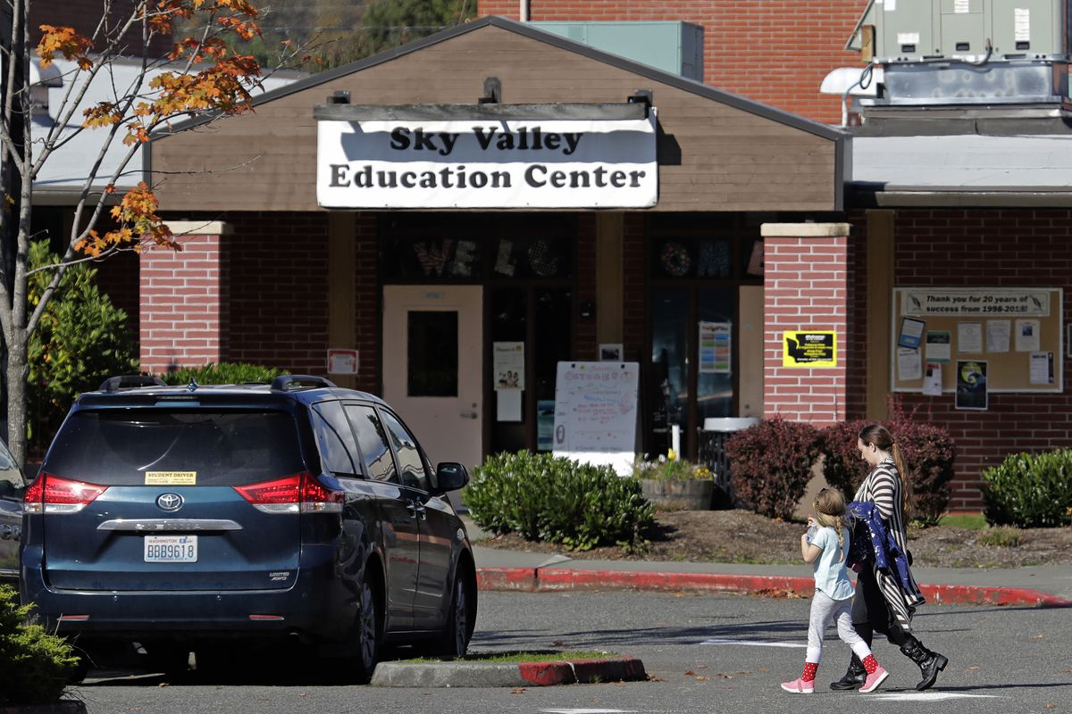In this Oct. 9, 2019, photo, people walk near an entrance to the Sky Valley Education Center in Monroe, Wash. A lawsuit filed on behalf of several families and teachers claims that officials failed to adequately respond to PCBs, or polychlorinated biphenyls, in the school. (AP Photo/Ted S. Warren)
