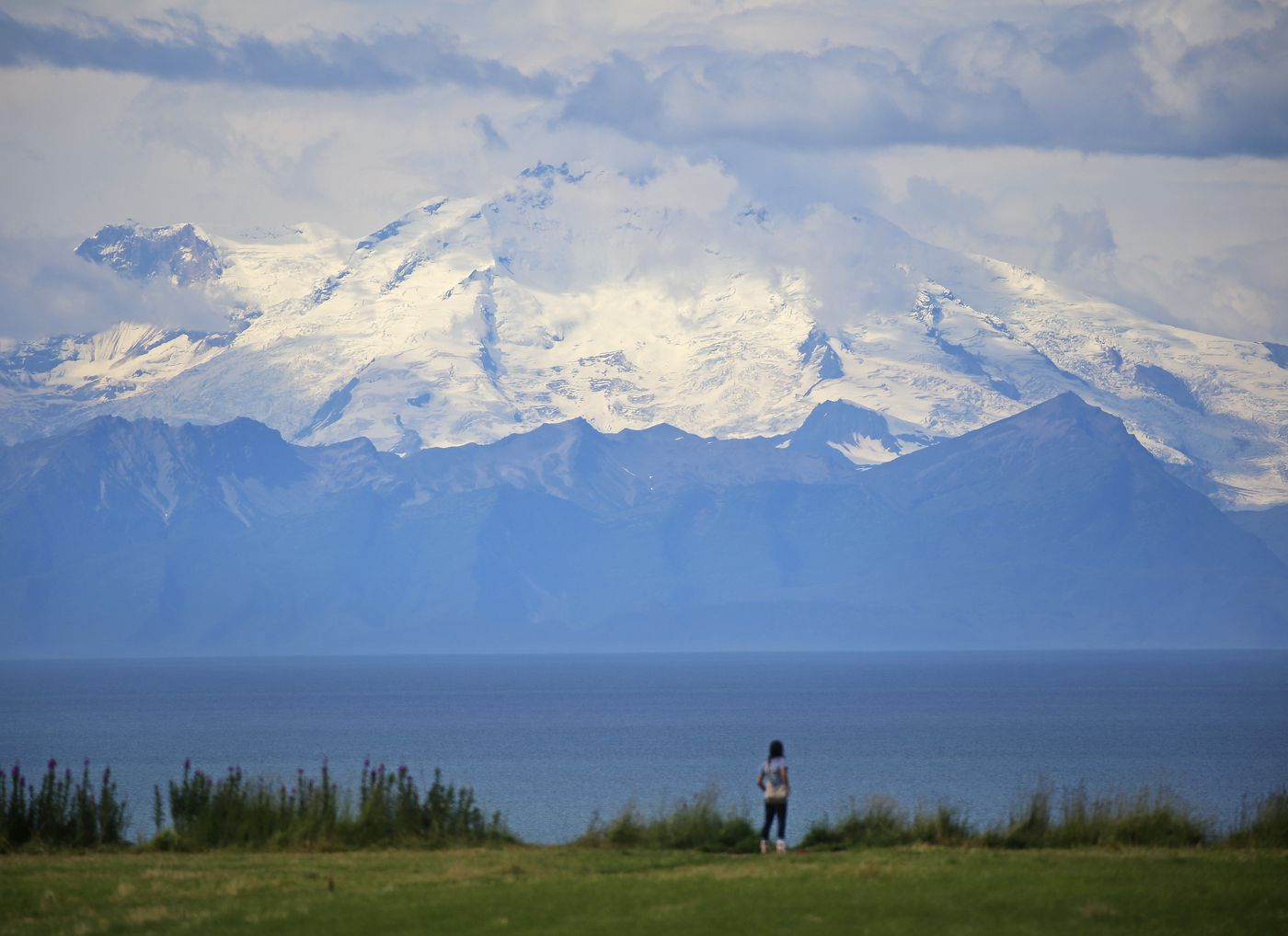 A woman takes one last look at Mount Redoubt before walking back to her vehicle at a pullout along the Sterling Highway, near Ninilchik, on Aug. 9, 2020. (Emily Mesner / ADN)