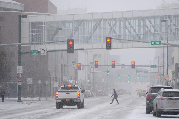 A pedestrian crosses 5th Avenue as snow began to fall in downtown Anchorage on Thursday, Nov. 9, 2017. (Bill Roth / Alaska Dispatch News)