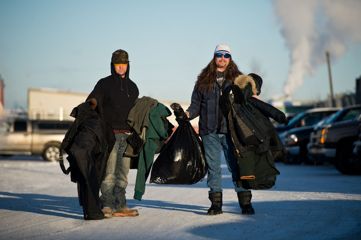 Wes Vent, left, and Chris Pruitt hold warm clothing on Wednesday that they intended to donate to homeless people. Both are recovering from addiction and have been giving to the homeless as part of their recovery process. Pruitt is a volunteer therapist and Vent is one of his clients. (Marc Lester / ADN)