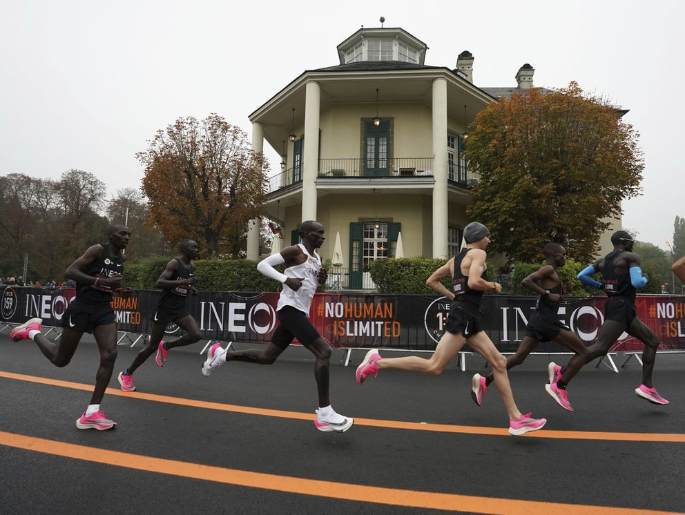 Eliud Kipchoge, white vest, runs past the Lusthaus with his pacemaking team in Vienna, Austria. Saturday, Oct. 12, 2019, during his attempt to run a sub two-hour marathon. (Andrew Baker /The INEOS 1:59 Challenge via AP)