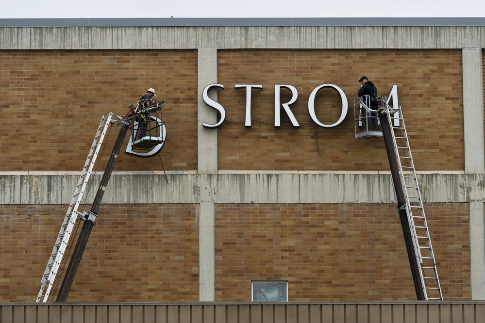 Glacier Sign workers Jason Welle, left, and Tommy Clark remove the lettering from the Nordstrom department store its last day in Anchorage on September 13, 2019. (Marc Lester / ADN)
