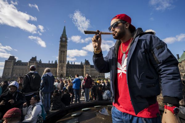 A resident smokes a large marijuana joint during the 420 Day festival on the lawns of Parliament Hill in Ottawa, Ontario, Canada, on April 20, 2018. MUST CREDIT: Bloomberg photo by Chris Roussakis