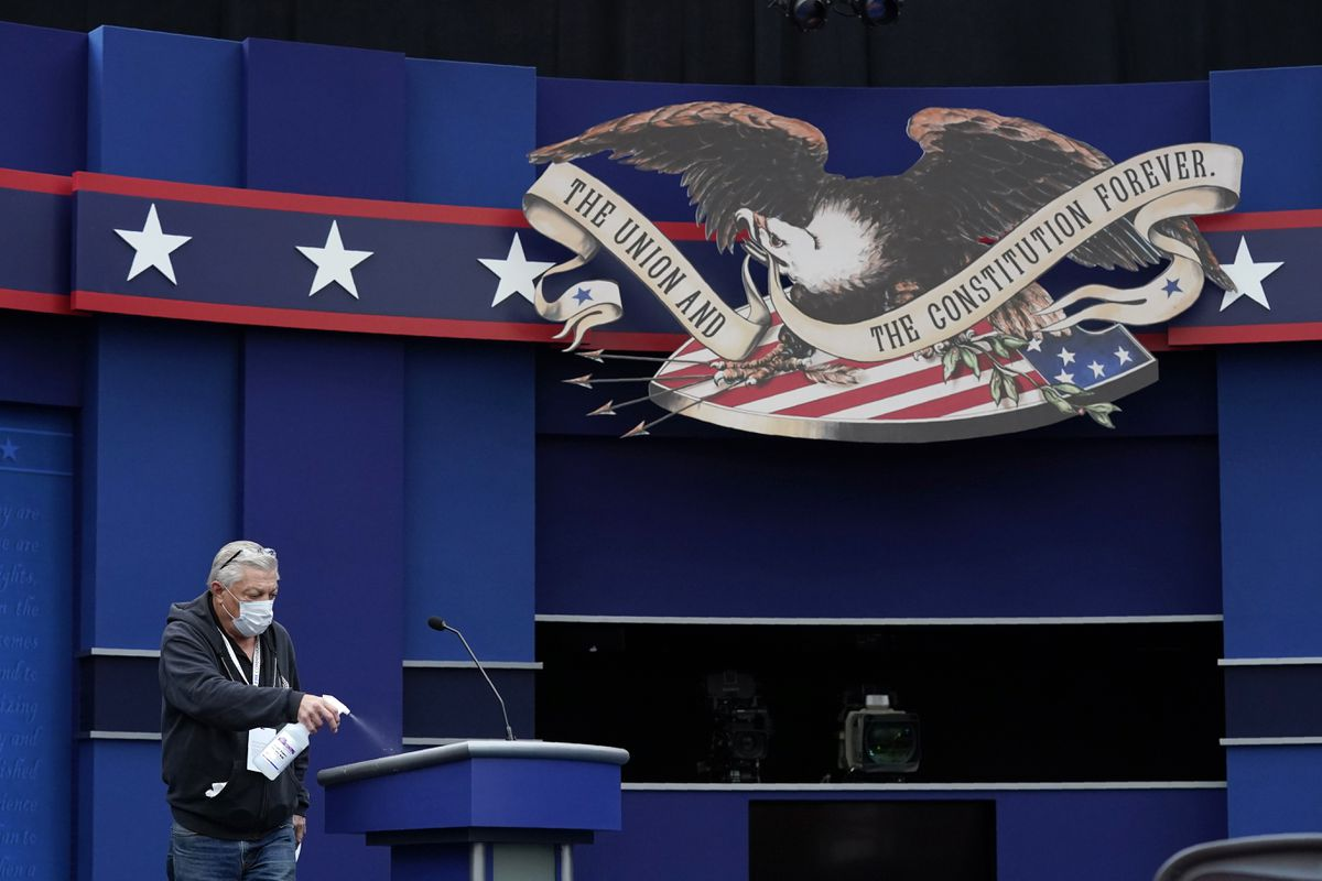 A worker sprays sanitizer on a lectern as preparations take place for the first Presidential debate in the Sheila and Eric Samson Pavilion, Monday, Sept. 28, 2020, in Cleveland. The first debate between President Donald Trump and Democratic presidential candidate, former Vice President Joe Biden is scheduled to take place Tuesday, Sept. 29. (AP Photo/Patrick Semansky)