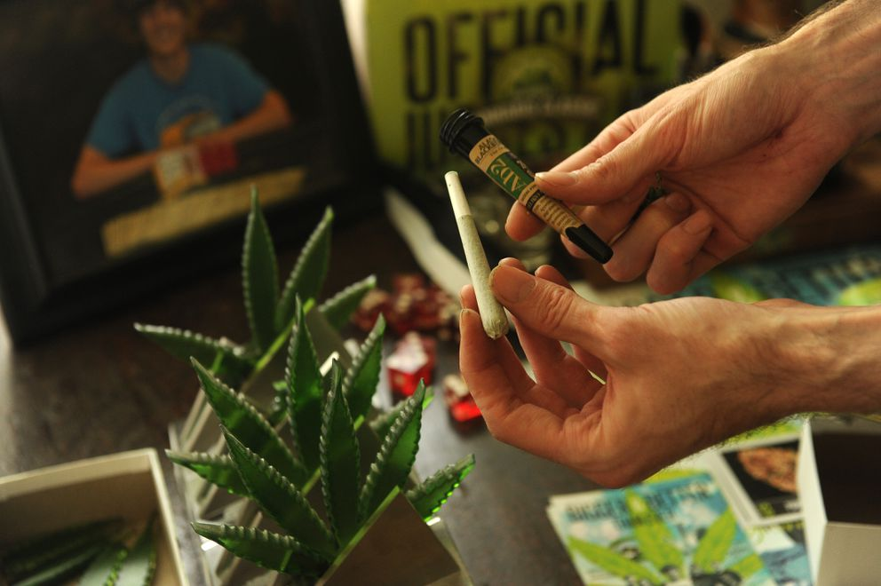 Cannabis breeder Evan Schlosberg holds a joint this past July in his Anchorage home from a strain he developed. (Bob Hallinen / Alaska Dispatch News)