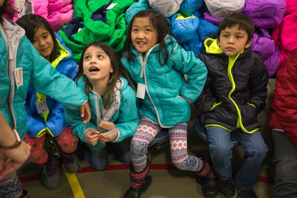 Creekside Elementary second graders, from left, Nicole Dela Rosa, Carmen Delgado, Angie Vue, and Isaac Saechao wear new coats Thursday, Nov. 9, 2017. Every student at the Title I school got a new coat, thanks to the Operation Warm program. (Loren Holmes / Alaska Dispatch News)