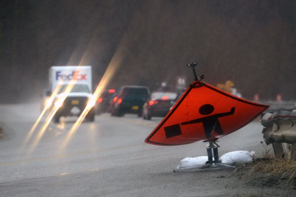 Gusting winds batter a flagman warning sign and drive rain sideways along Turnagain Arm on Monday afternoon, February 16, 2015, on the Seward Highway. (Erik Hill / ADN)