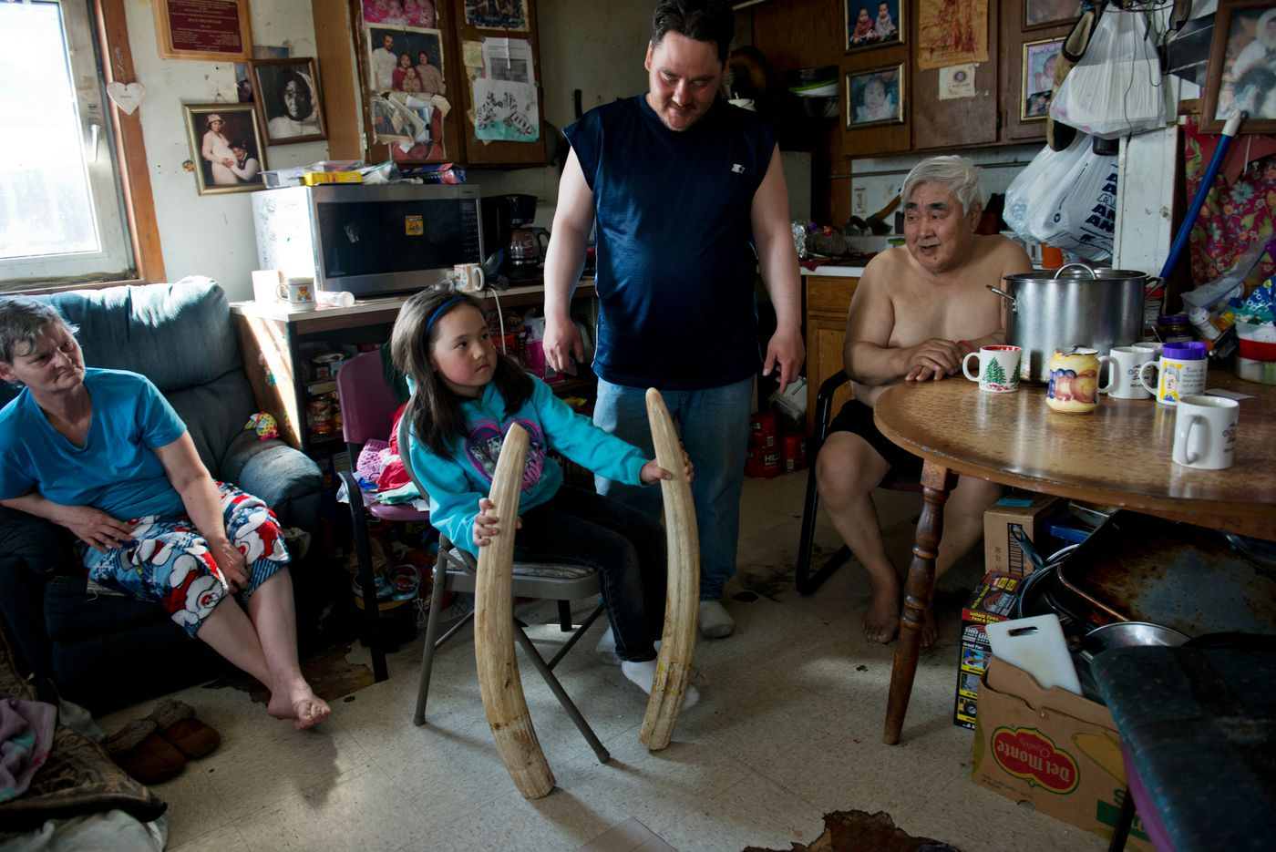 Six-year-old Winter Pelowook holds up ivory from a walrus hunted by her father, Carl Pelowook Jr., at their Savoonga homelast month. Carl's mother, Jean Pelowook, is at left and father, Carl Pelowook Sr., is at right. (Marc Lester / Alaska Dispatch News)