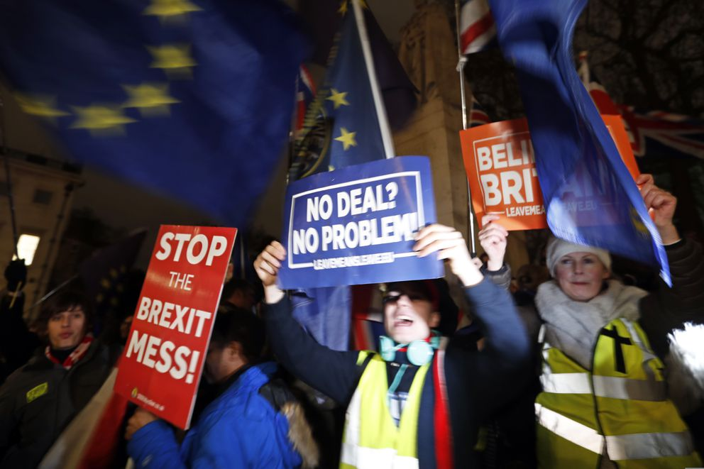 Leavers, center right, hold signs next to Pro-European demonstrators at Parliament Square in London, Tuesday, Jan. 15, 2019. Britain's Prime Minister Theresa May is struggling to win support for her Brexit deal in Parliament. Lawmakers are due to vote on the agreement Tuesday, and all signs suggest they will reject it, adding uncertainty to Brexit less than three months before Britain is due to leave the EU on March 29. (AP Photo/Frank Augstein)