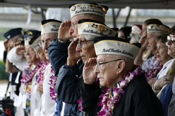 Pearl Harbor survivors salute during the National Anthem at a ceremony in Pearl Harbor, Hawaii on Friday, Dec. 7, 2018 marking the 77th anniversary of the Japanese attack. The Navy and National Park Service jointly hosted the remembrance ceremony at a grassy site overlooking the water and the USS Arizona Memorial. (AP Photo/Audrey McAvoy)