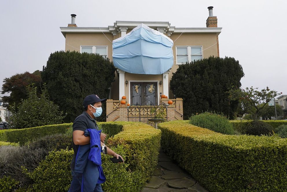 A man walks past a large face mask hanging over pumpkins in front of a house during the coronavirus pandemic in San Francisco. (AP Photo/Jeff Chiu, File)
