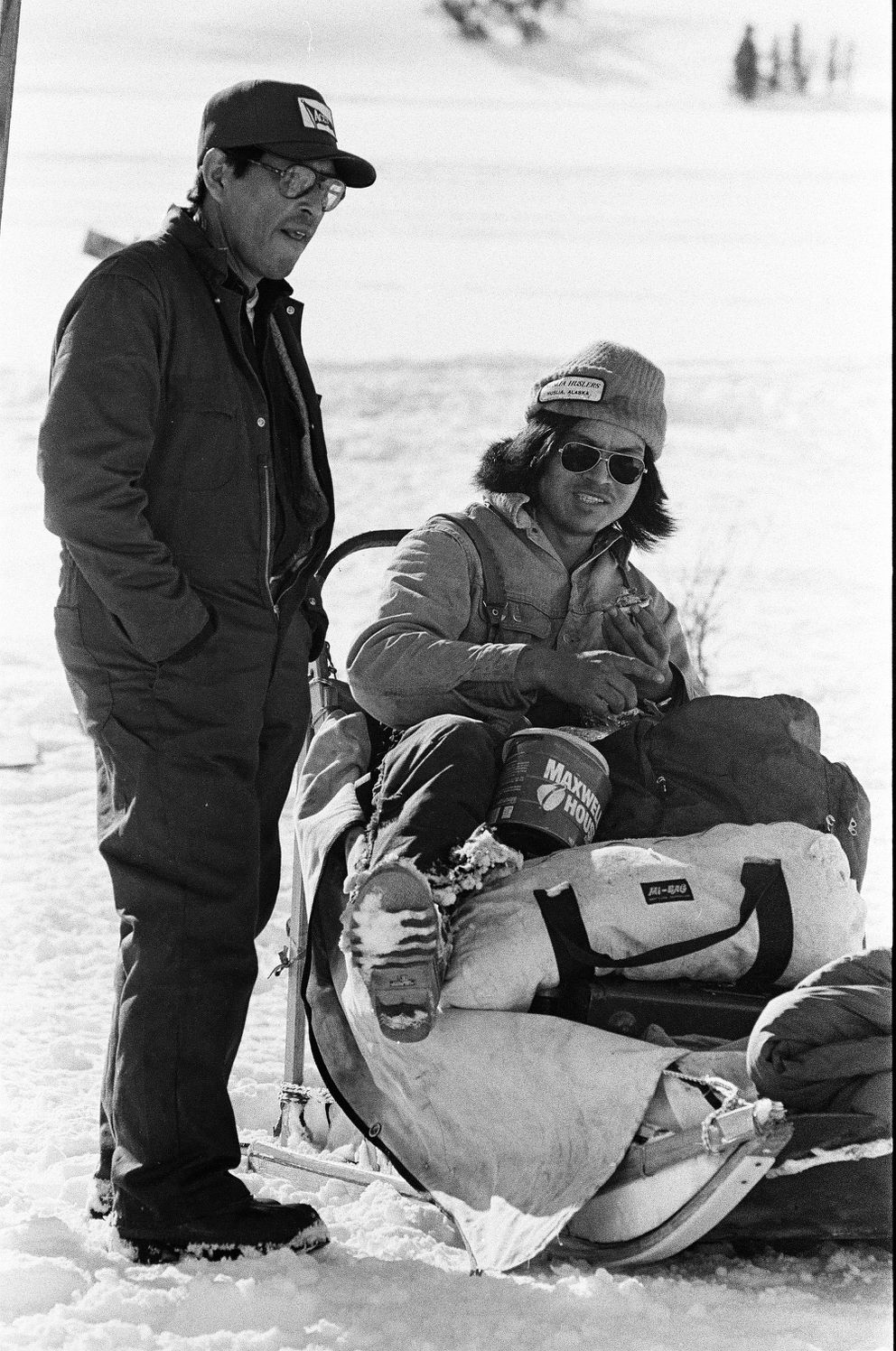 Emmitt Peters and Gary Attla visit at the Rainy Pass checkpoint during the 1981 Iditarod Trail Sled Dog Race on March 9, 1981. (Marc Olson / ADN archive)