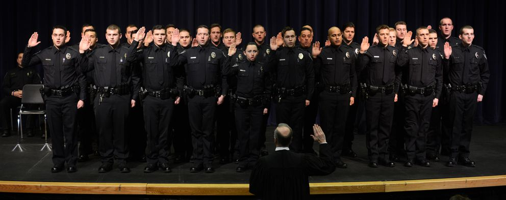 The Honorable J. Patrick Hanley administers the oath. The 26 new officers now move on to field training. (Erik Hill / Alaska Dispatch News)