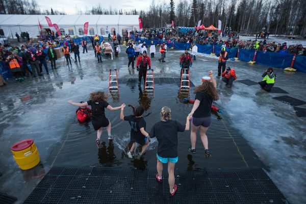 A team from Chugiak High School jumps into Goose Lake on Saturday, Dec. 16, 2017 for the 9th annual Special Olympics Alaska Polar Plunge. The organization, which provides year-round sports training and athletic competition to individuals with intellectual disabilities, typically raises over $300,000 from the event. (Loren Holmes / ADN)