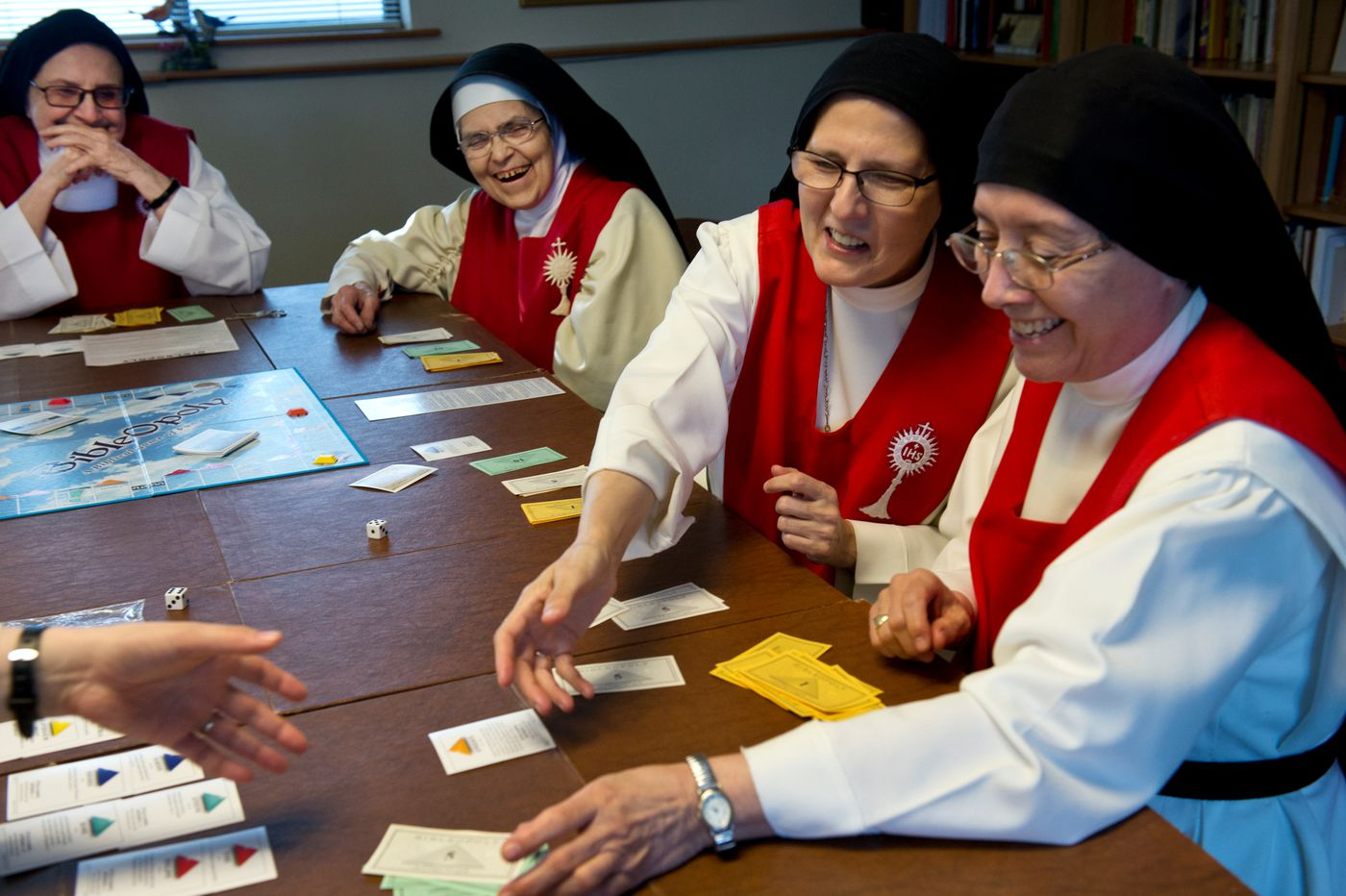 The Sisters of Perpetual Adoration play a board game called Bibleopoly during their recreation time on April 2. From left are Sister Alicia Valencia, Sister Milagrosa Veytia, Sister Evelia Martinez and Sister Catalina Marcor. (Marc Lester / ADN)