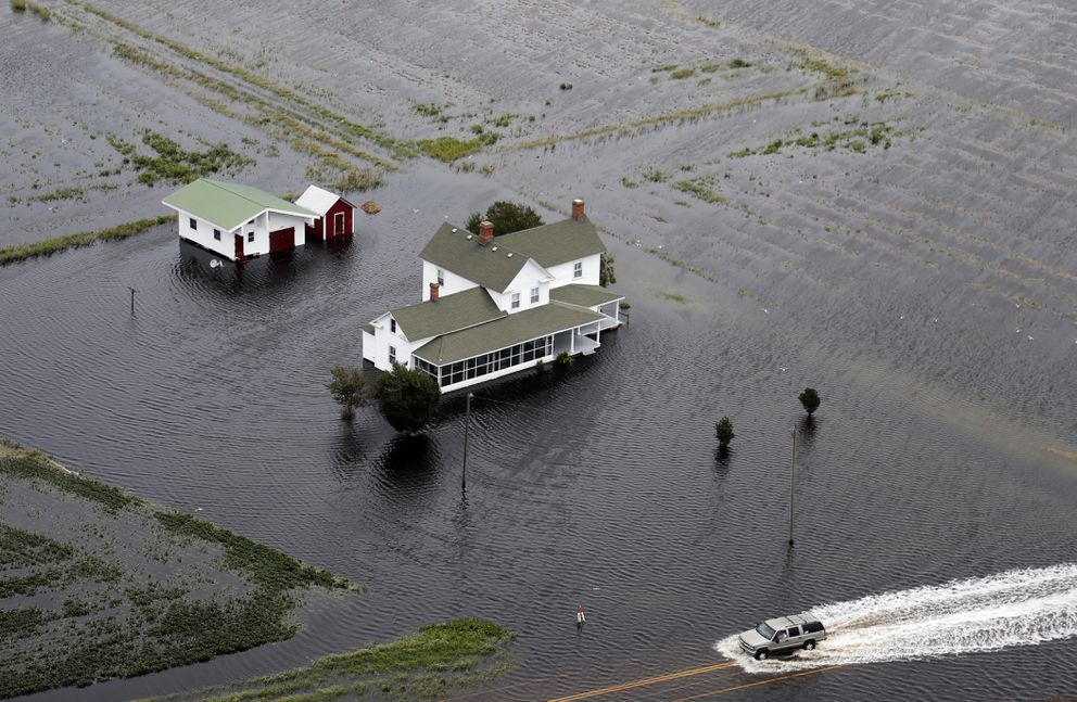 A pickup truck drives on a flooded road past a farm house that is surrounded by flooded fields from tropical storm Florence in Hyde County, NC., Saturday, Sept. 15, 2018. (AP Photo/Steve Helber)