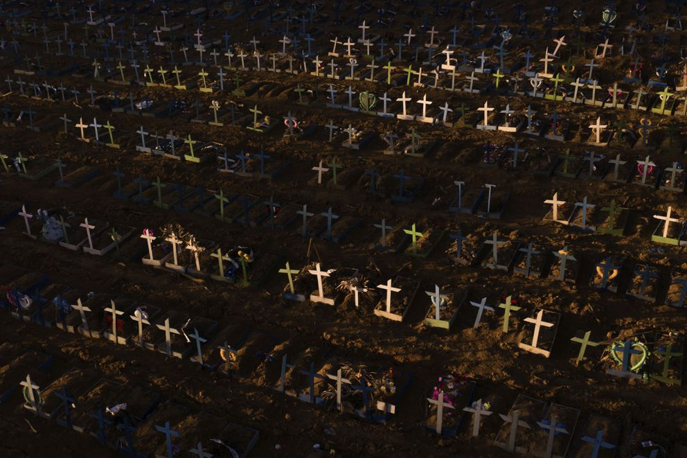 Crosses mark the graves of those who have passed away since early April, filling a new section of the Nossa Senhora Aparecida public cemetery amid the new coronavirus pandemic in Manaus, Brazil, Sunday, May 16, 2020. The new area was opened last month to cope with a sudden surge in deaths in the city, though most of the deceased were not tested for COVID-19. (AP Photo/Felipe Dana)