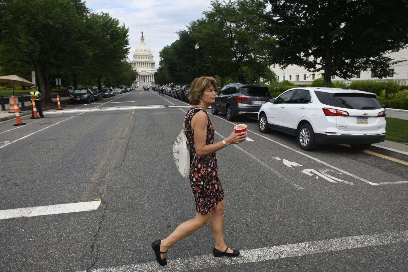 Carrying a bag filled with folders of papers she calls her 'homework ' and smoothie to drink, Sen. Lisa Murkowski begins her day with a walk from her Capitol Hill home toward her office on June 18, 2019. (Marc Lester / ADN)