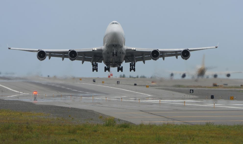 An Atlas Air Boeing 747 freighter takes off towards the east at Ted Stevens Anchorage International Airport on Monday, July 9, 2018, as a Polar Air Cargo jet taxis for take off. (Bill Roth / ADN)