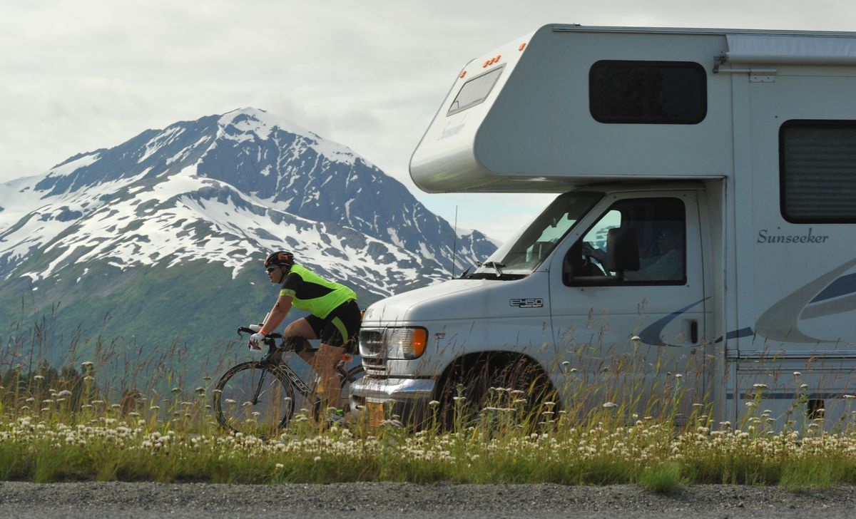 An Alaskaman Extreme Triathlon competitor bikes along the Seward Highway as a motorhome passes by south of Girdwood on July 15, 2017. (Bob Hallinen / ADN archive)