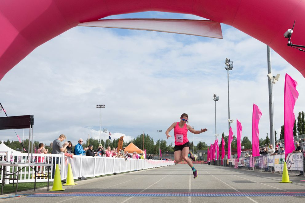 Kikkan Randall does her signature finish-line jump as she completes the 2019 Alaska Run for Women in third place -- a little more than a year after her 2018 breast cancer diagnosis. Randall finished the five-mile race in a time of 29:29. (Loren Holmes / ADN)