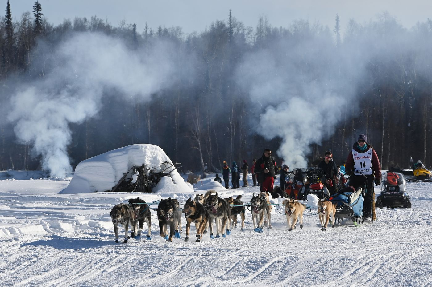 Ryne Olson drives her dog team past campfires on the Susitna River during the start of the Iditarod. (Bill Roth / ADN)