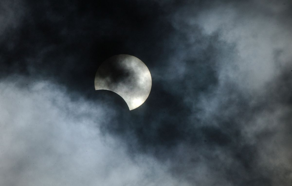 A partial solar eclipse visible through clouds over Anchorage in 2002.(Bill Roth / Alaska Dispatch News)
