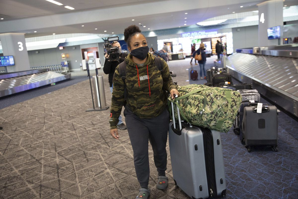 U.S. Navy member Estfhi Guzman picks up her baggage after arriving at LaGuardia Airport from Miami on the first Boeing 737 Max flight since the plane's return to service on Tuesday, Dec. 29, 2020, in New York. American Airlines is the first carrier to fly the recertified 737. (AP Photo/Kevin Hagen).