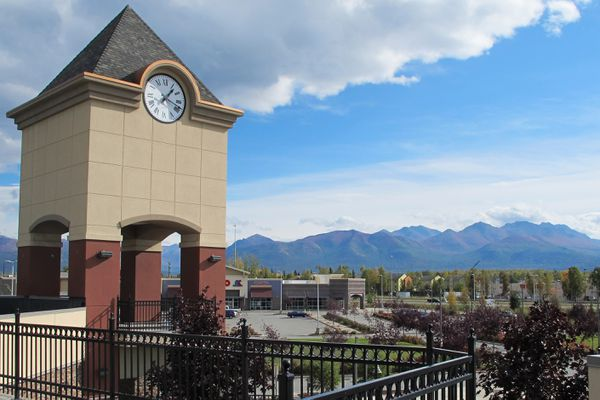 This clock tower is in one of four buildings that make up Glenn Square, as seen on September 10, 2015. It is the complex's centerpiece that can easily be seen from the Glenn Highway near Mountain View Drive. The Chugach Mountains provide an Alaskan backdrop for the commercial district in north Anchorage. (Scott Jensen / ADN)