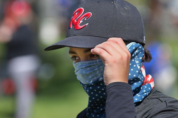 In this Saturday, May 9, 2020 photo, St. Louis RiverCats youth baseball player Carter Herrin, 13, from House Springs, wears a face covering during the Mother's Day Classic baseball tournament organized by GameTime Tournaments in Cottleville, Mo..