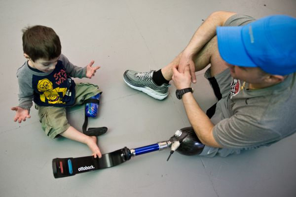 Justus Bohart, 3, of Seward, talks with Jeremy Maddamma at The Dome on March 23, 2018. Bohart's mother, Rhonda Bohart, said she likes to bring Justus to events where he can meet with active amputees. Prosthetics manufacturer Ottobock hosted a clinic at The Dome on March 23, 2018. The event allowed amputees the chance to try prosthetics designed for running and speak with company clinicians and technicians. Ottobock also planned to host an event at Alyeska Resort on Saturday, March 24, to allow people to try prostheses designed for skiing and snowboarding. (Marc Lester / ADN)