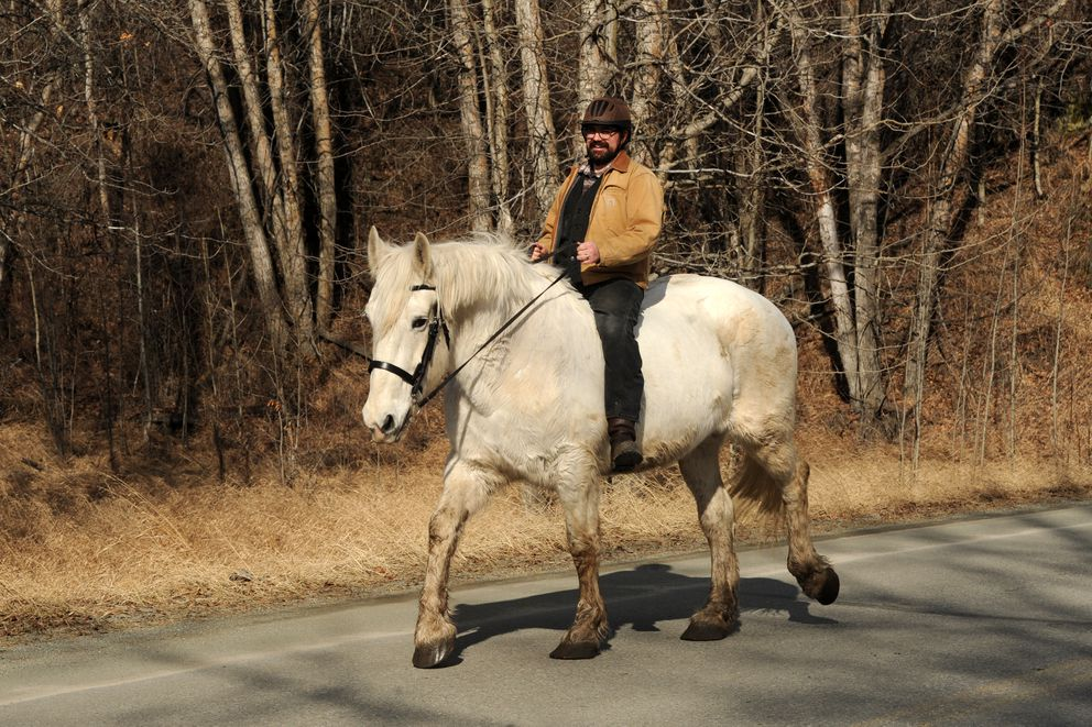 """Keith Barkwood rides a Percheron draft horse named Bella along Bodenburg Loop in Butte. Bella belongs to a neighbor, but Barkwood rides and grooms the horse often. """"I love the view from up here,"""" he said. (Erik Hill / ADN archive 2016)"""