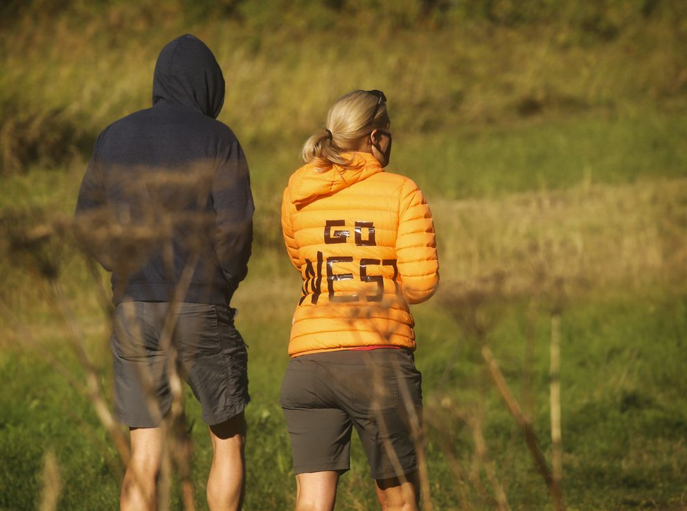 Shannon Donley, right, shows her allegiance as walks along the trail to watch her kids race. (Emily Mesner / ADN)