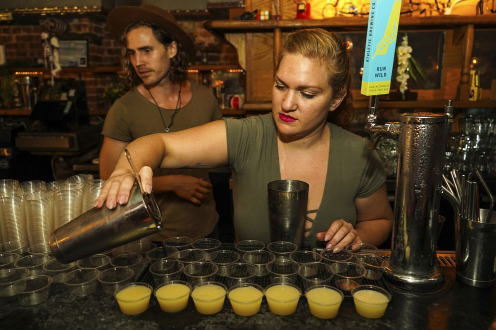 """This undated image released by Sasha Charoensub shows bartenders Matthew Bray, left, looking on while Crystal Chasse preparing mocktails at Listen bar in New York. Alcohol-free bars serving elevated """"mocktails"""" are attracting more young people than ever before. Regular bars and restaurants are cluing into the idea that alcohol-free customers want more than a splash of cranberry with a spritz. The interest is also driven by the wellness movement and higher quality ingredients. (Sasha Charoensub/Listen Bar via AP)"""