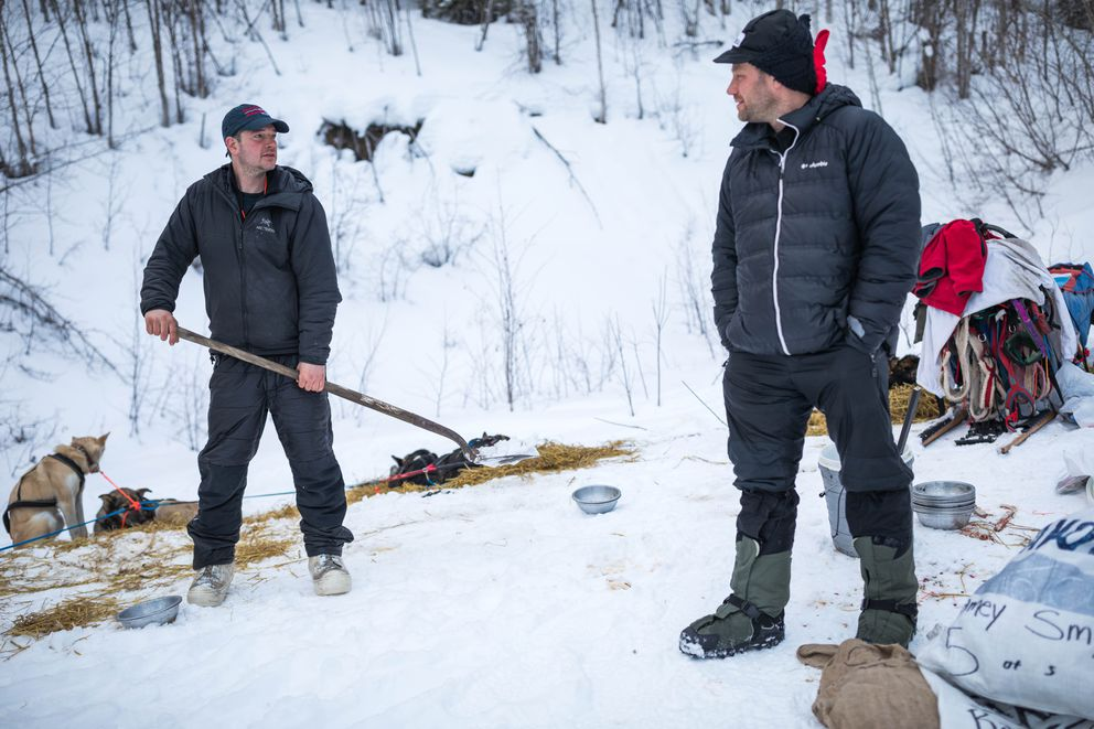 Ray Redington Jr., left, scoops dog poop while talking with fellow musher Ramey Smyth at the Takotna checkpoint last week. (Loren Holmes / ADN)