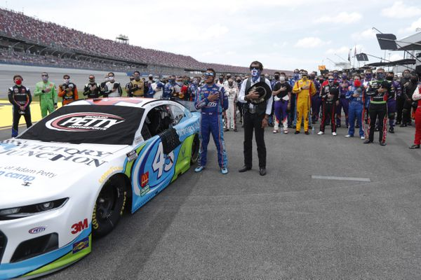Driver Bubba Wallace, front left, and team owner Richard Petty, front right, stand for the National Anthem in the pits of the Talladega Superspeedway prior to the start of the NASCAR Cup Series auto race at the Talladega Superspeedway in Talladega Ala., Monday June 22, 2020. In an extraordinary act of solidarity with NASCAR's only Black driver, dozens of drivers pushed the car belonging to Bubba Wallace to the front of the field before Monday's race as FBI agents nearby tried to find out who left a noose in his garage stall over the weekend. (AP Photo/John Bazemore)