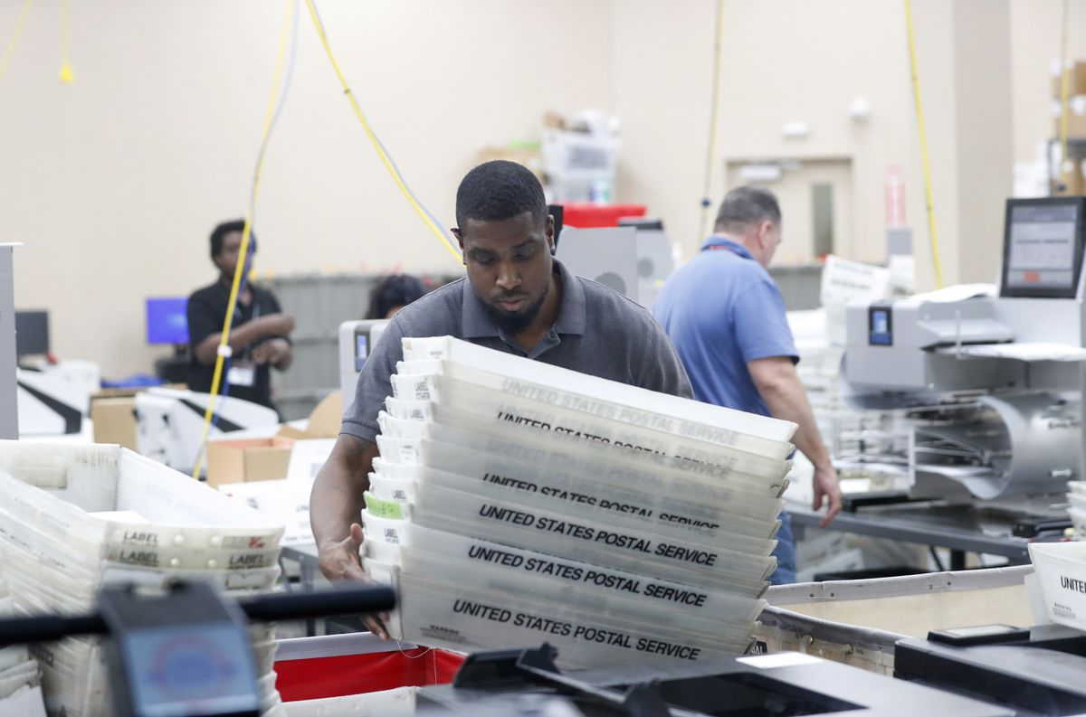 An employee at the Broward County Supervisor of Elections office picks up bins containing ballots as he counts ballots from the mid-term election, Thursday, Nov. 8, 2018, in Lauderhill, Fla. (AP Photo/Wilfredo Lee)