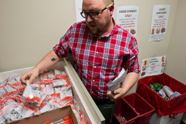 Matt Allen, HIV prevention and education coordinator for Four A's, shows some of the syringes and other supplies that the organization distributes, on Aug. 29. The program accepts used syringes for proper disposal and distributes clean syringes, metal cookers, cotton balls, tourniquets and alcohol swabs. (Marc Lester / Alaska Dispatch News)