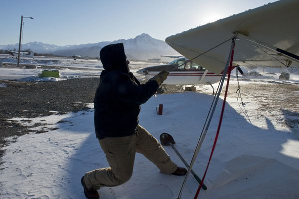 Don Hammond, one of the owners of Fly Around Alaska, cinches a Piper Super Cub down at the Palmer Airport during a windstorm on Jan. 29, 2018. (Marc Lester / ADN)