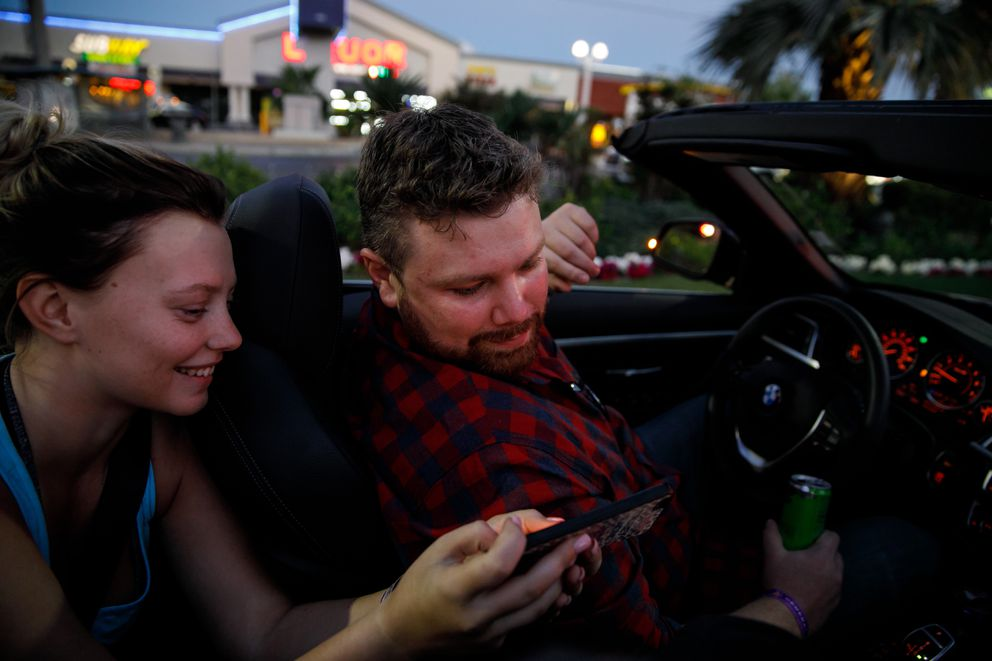 Kamryn Trubey shows Brian MacKinnon photos of his childhood friend, Adrian Murfitt as they take drive around in Murfitt's rental car in Las Vegas two days after he died in MacKinnon's arms. (Marcus Yam/Los Angeles Times/TNS)